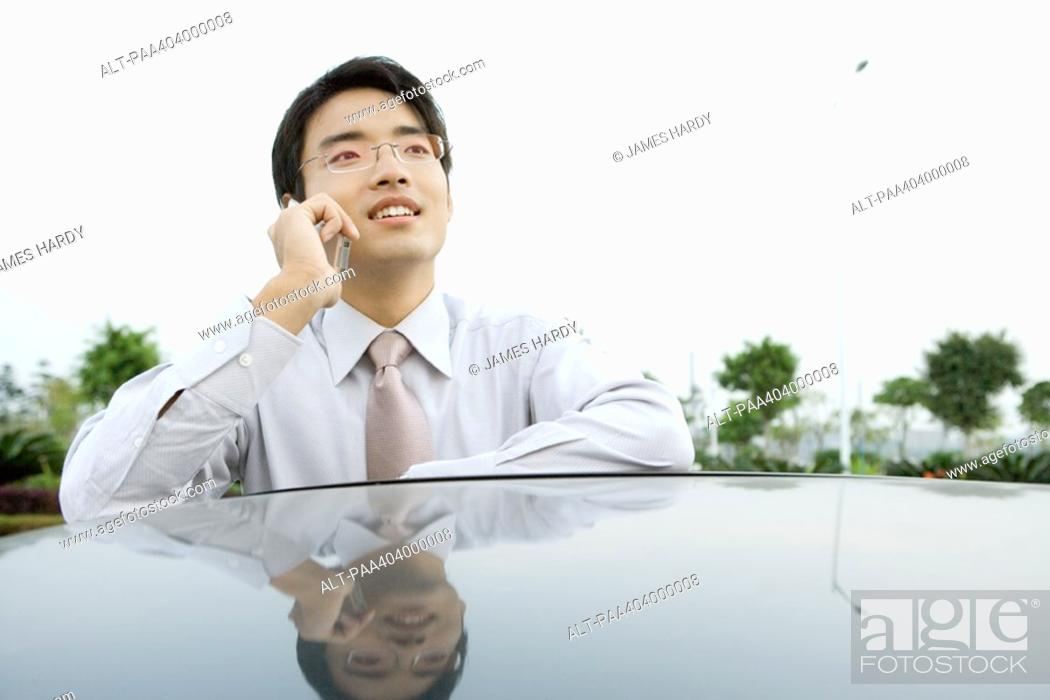 Stock Photo: Businessman leaning against car, using cell phone.