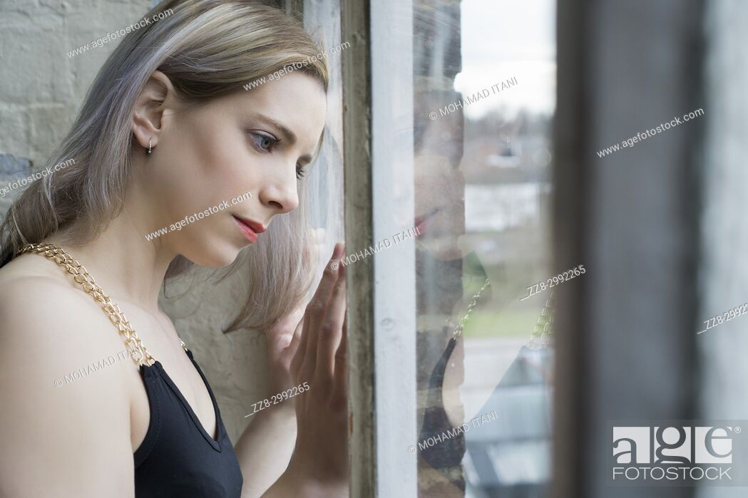 Stock Photo: Portrait of a beautiful blond woman looking out of the window.