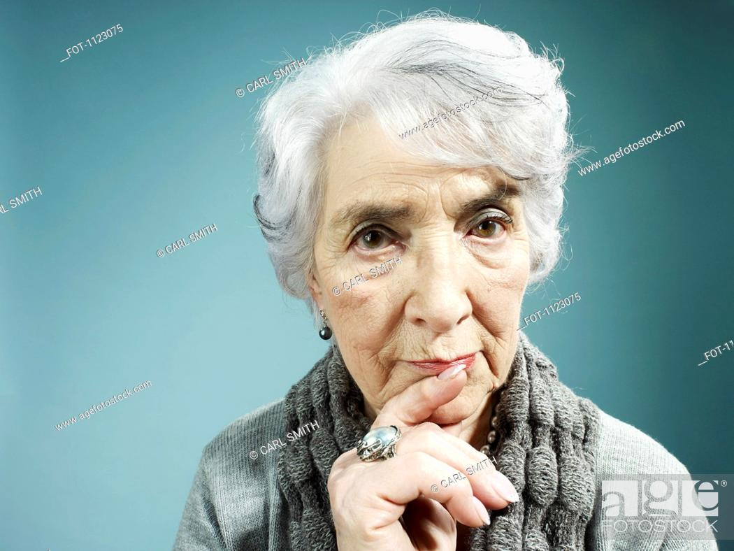 Stock Photo: A senior woman thinking with her index finger to her lips.