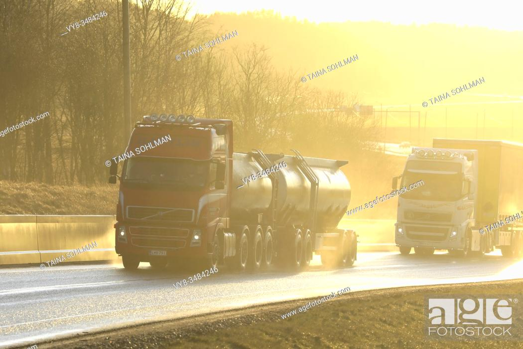 Imagen: Two Volvo FH trucks, red tanker and white semi pulling freight trailer on wet road in natural, in-camera golden light. Salo, Finland. January 24, 2020.