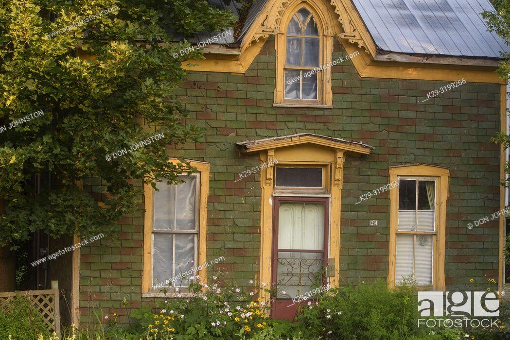 Stock Photo: Summer flowers overgrowing an old house along mainstreet, Kirkton, Ontario, Canada.