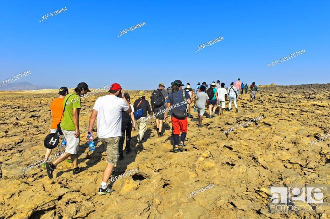 Photo de stock: Overtourism, groups of tourists on the way to the Dallol caldera, one of the most inhospitable and barren place on earth, geothermal field of Dallol.