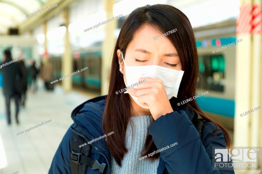 Stock Photo: Woman wearing face mask at train platform.