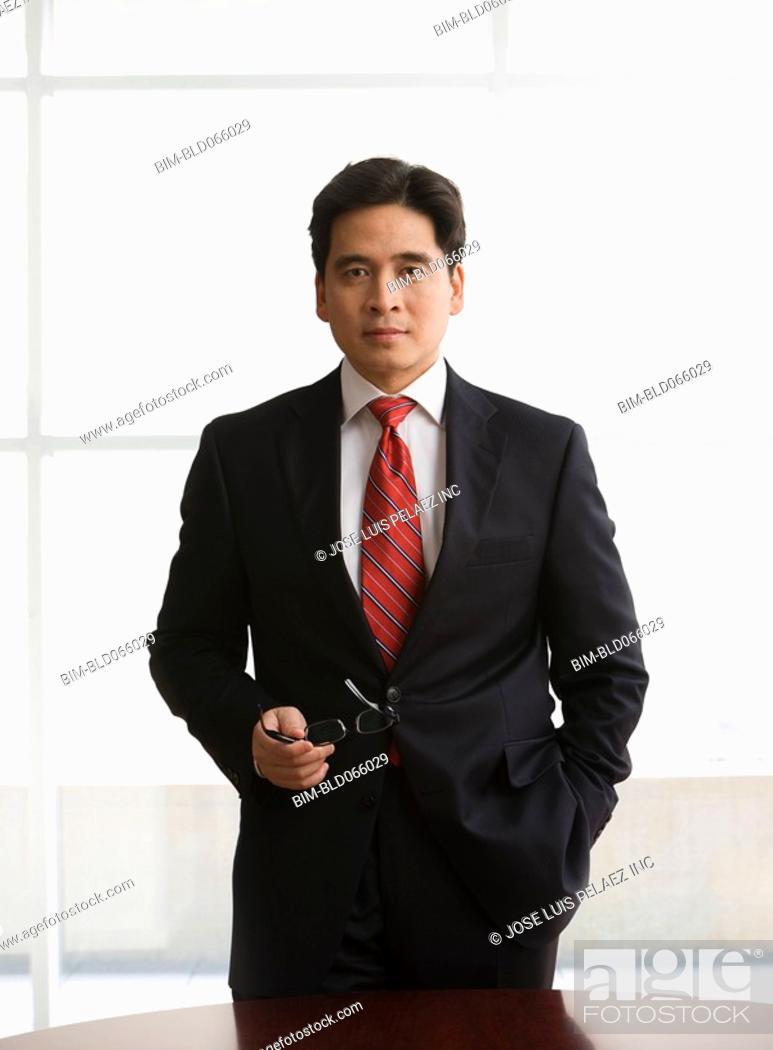 Stock Photo: Chinese businessman holding eyeglasses.
