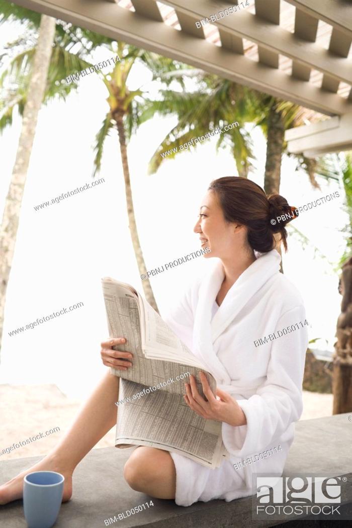 Stock Photo: Asian woman in bathrobe reading newspaper.