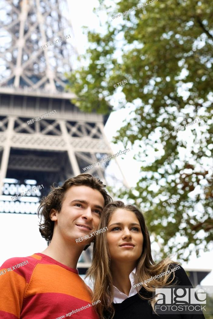 Stock Photo: Young couple standing under Eiffel tower, Paris, France.