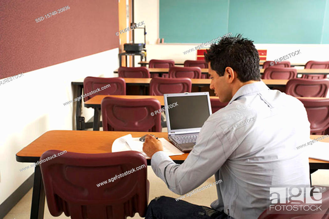 Stock Photo: Rear view of a college student sitting in a lecture hall in front of a laptop.