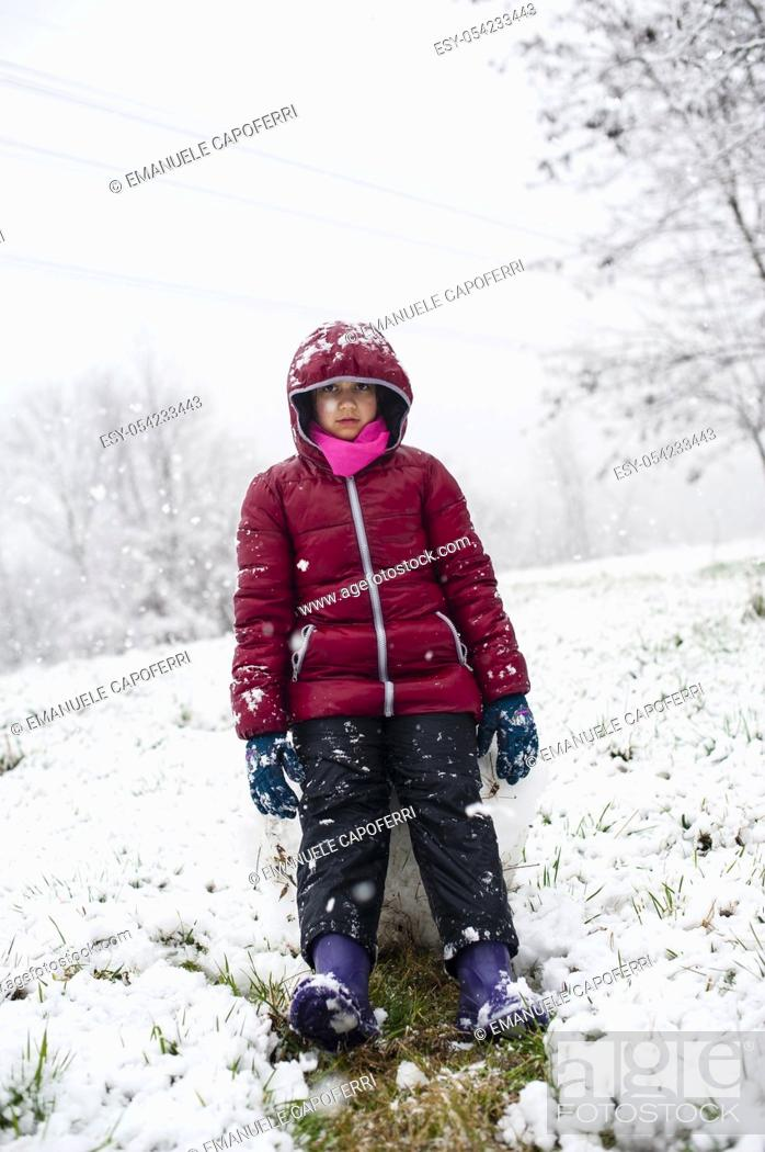 Stock Photo: Little girl sitting on a pile of snow.