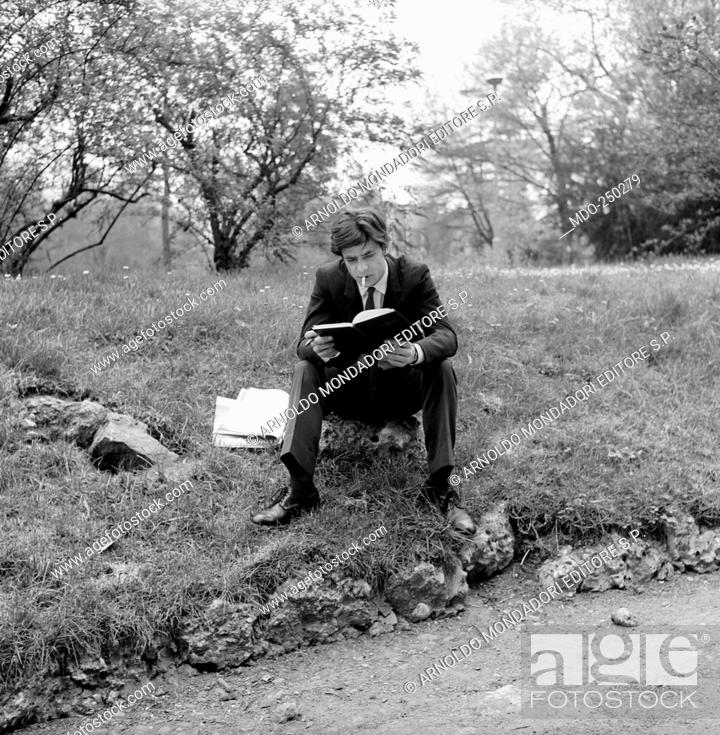 Stock Photo: Giancarlo Giannini, seated on a stone, consults the diary. Actor Giancarlo Giannini, seated on a stone in a meadow, smokes a cigarette and consults his diary.
