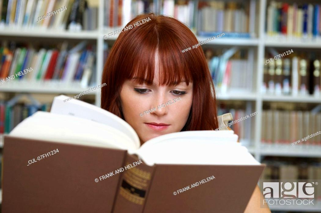 Stock Photo: Young woman reading in library.