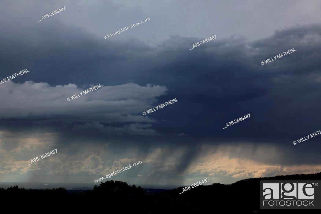 Imagen: Descending dark wall cloud with heavy rainfall above forest, Bavaria, Germany, Europe.