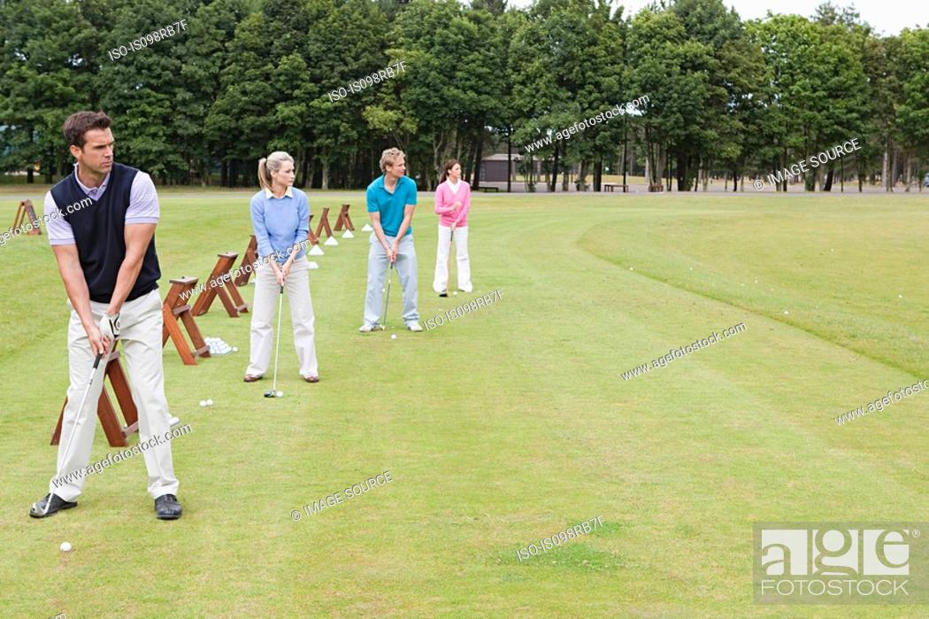 Stock Photo: Four golfers on a driving range.
