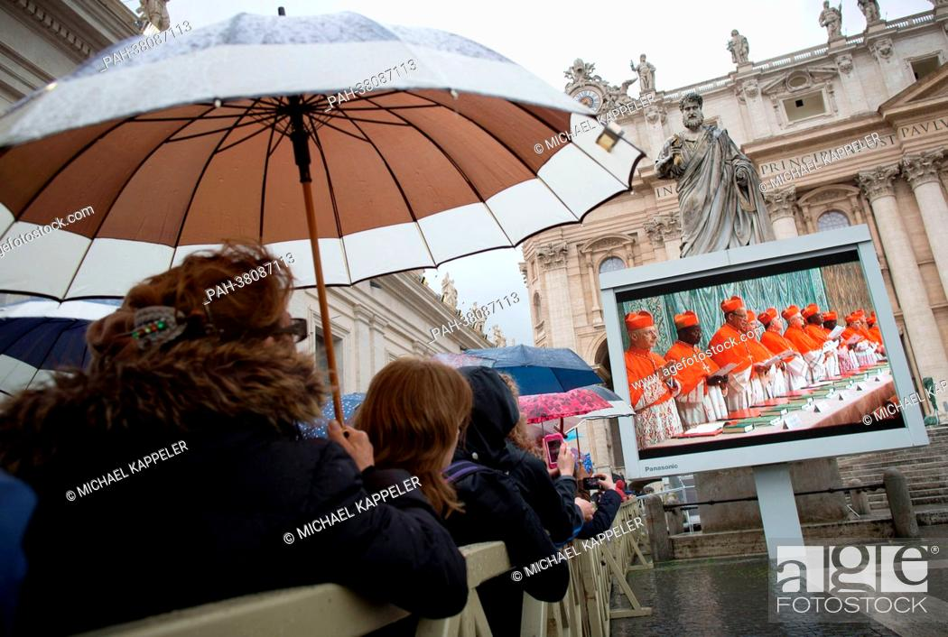 Stock Photo: Pilgrims watch the entrance of the Cardinals into the Sistine Chapel on video monitors on St. Peter's Square in Vatican City, Vatican, 12 March 2013.
