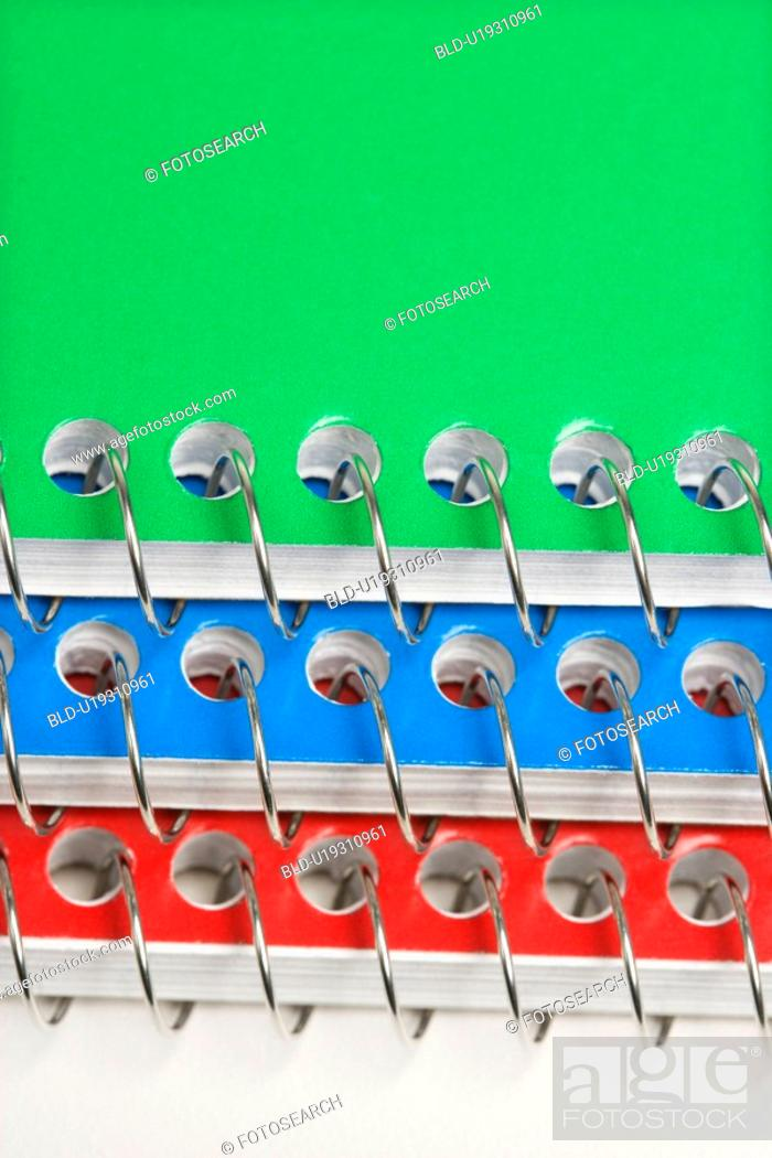 Stock Photo: Close up of three spiral bound notebooks stacked up.