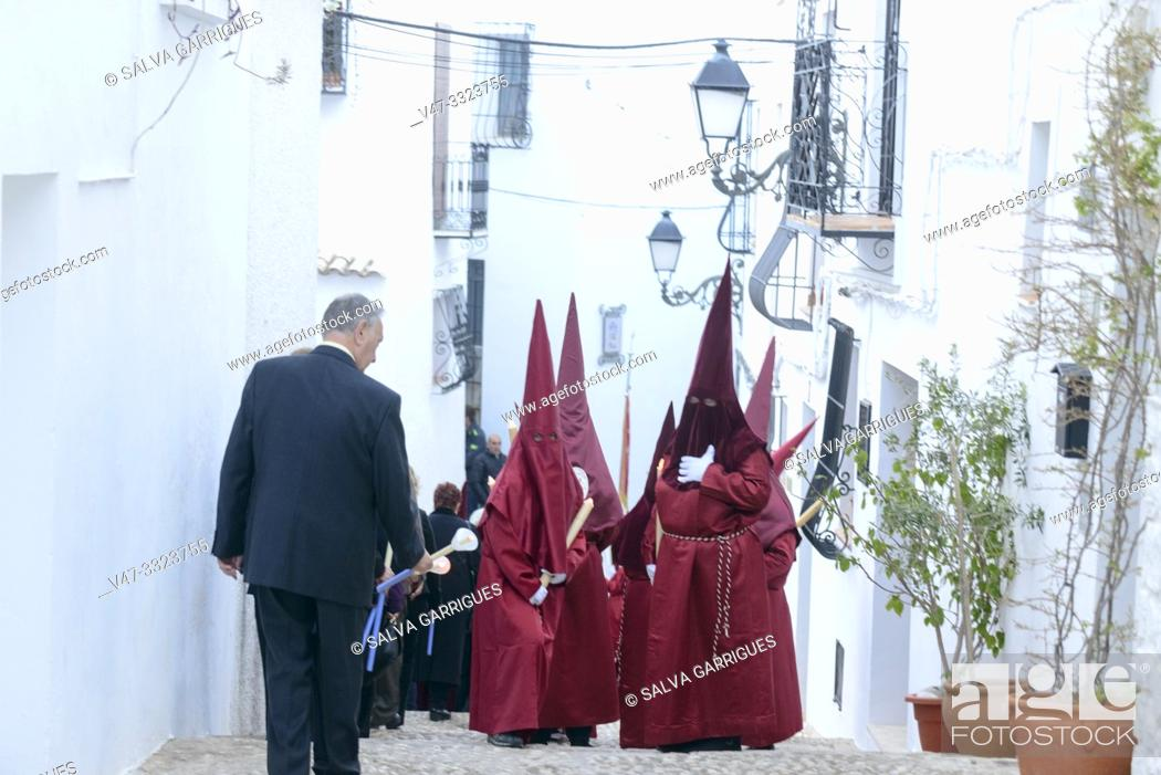 Imagen: Cofrades with the tunic and the red procession cap through the streets of Altea.