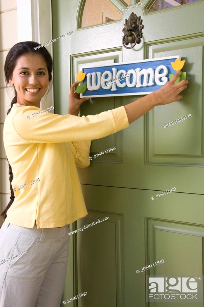 Stock Photo: Mixed Race woman hanging Welcome sign.