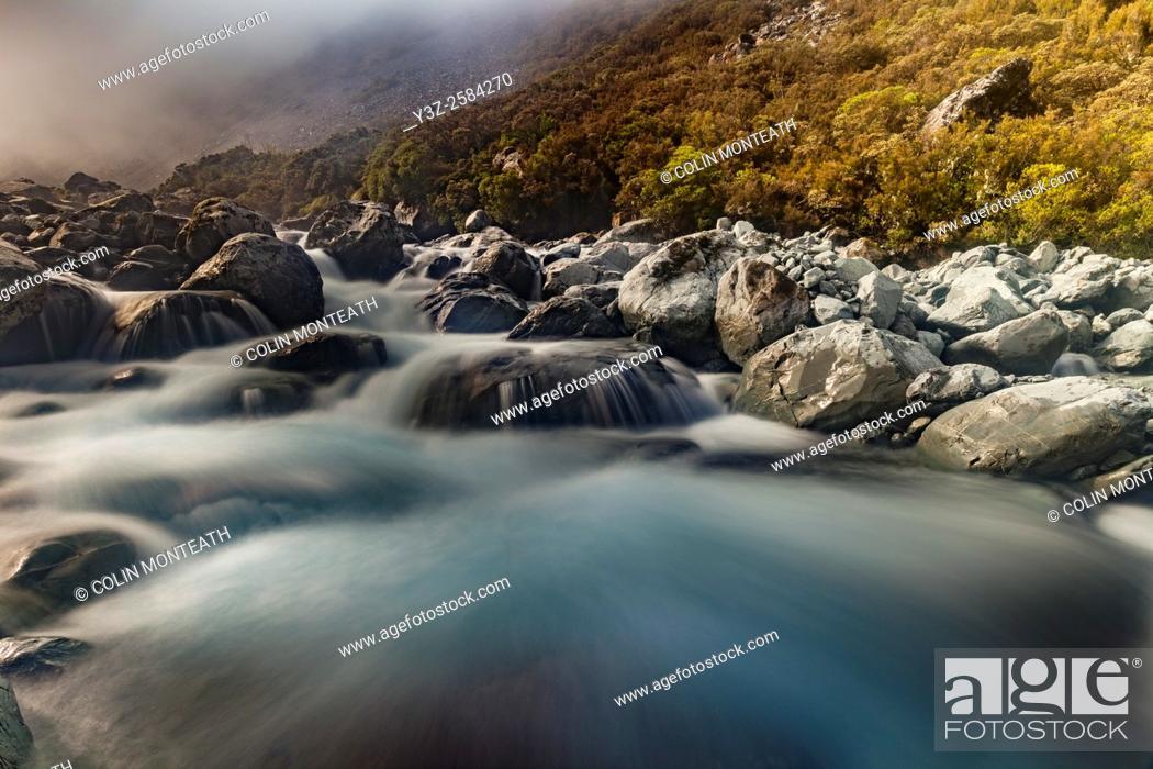 Imagen: Mungo river rapids, afternoon light breaks through heavy mist, West Coast, New Zealand.