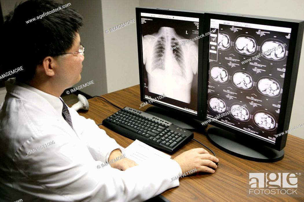 Stock Photo: Doctor examining MRI scans.
