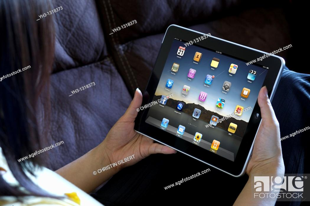 Stock Photo: A woman hand holding an ipad showing iPad applications screen.