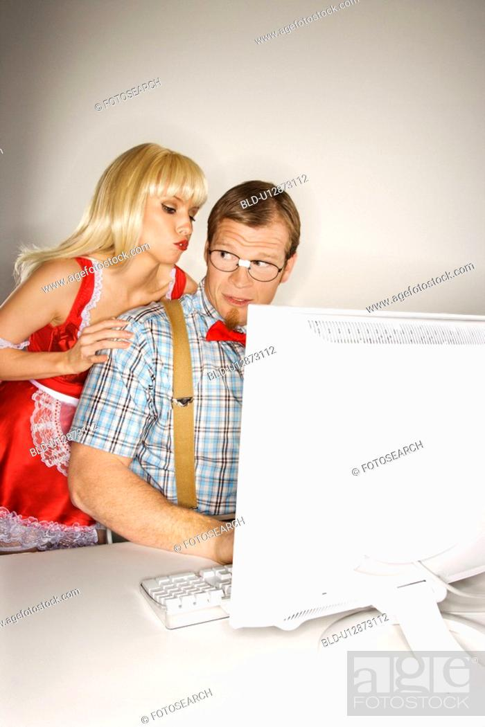Stock Photo: Man dressed like nerd at computer looking over shoulder at woman.