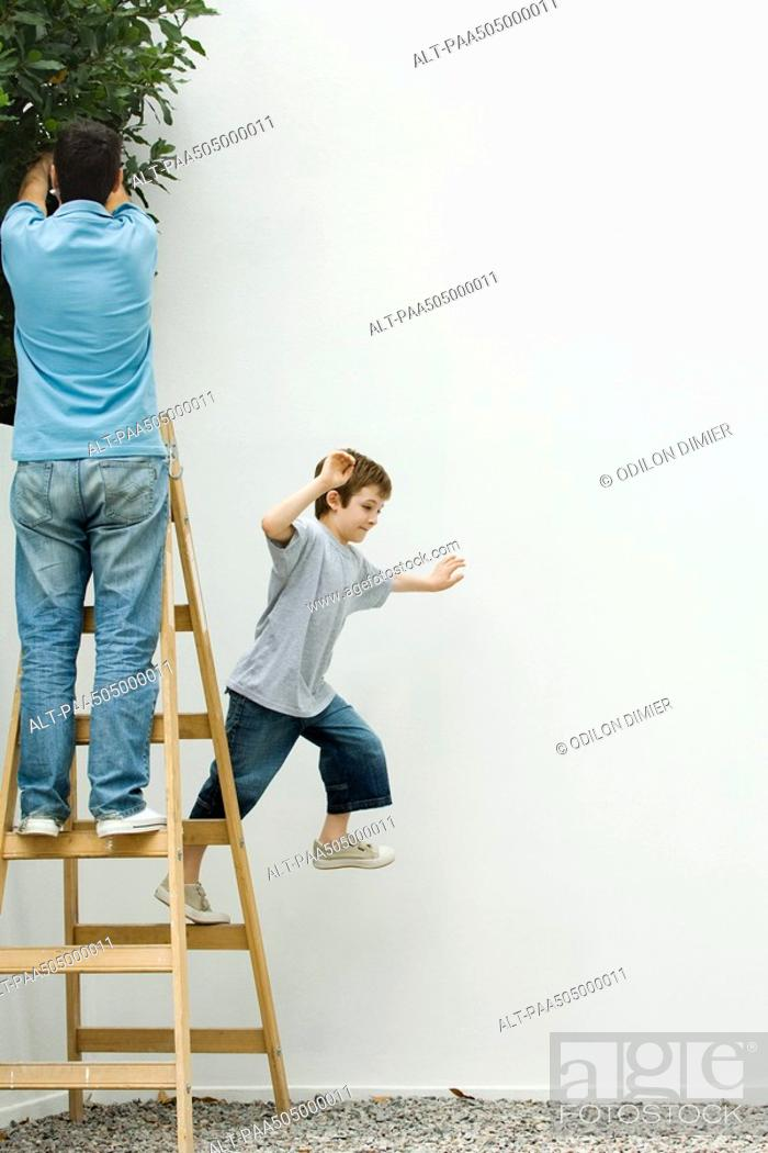 Stock Photo: Father and son standing on ladder, boy leaping off.