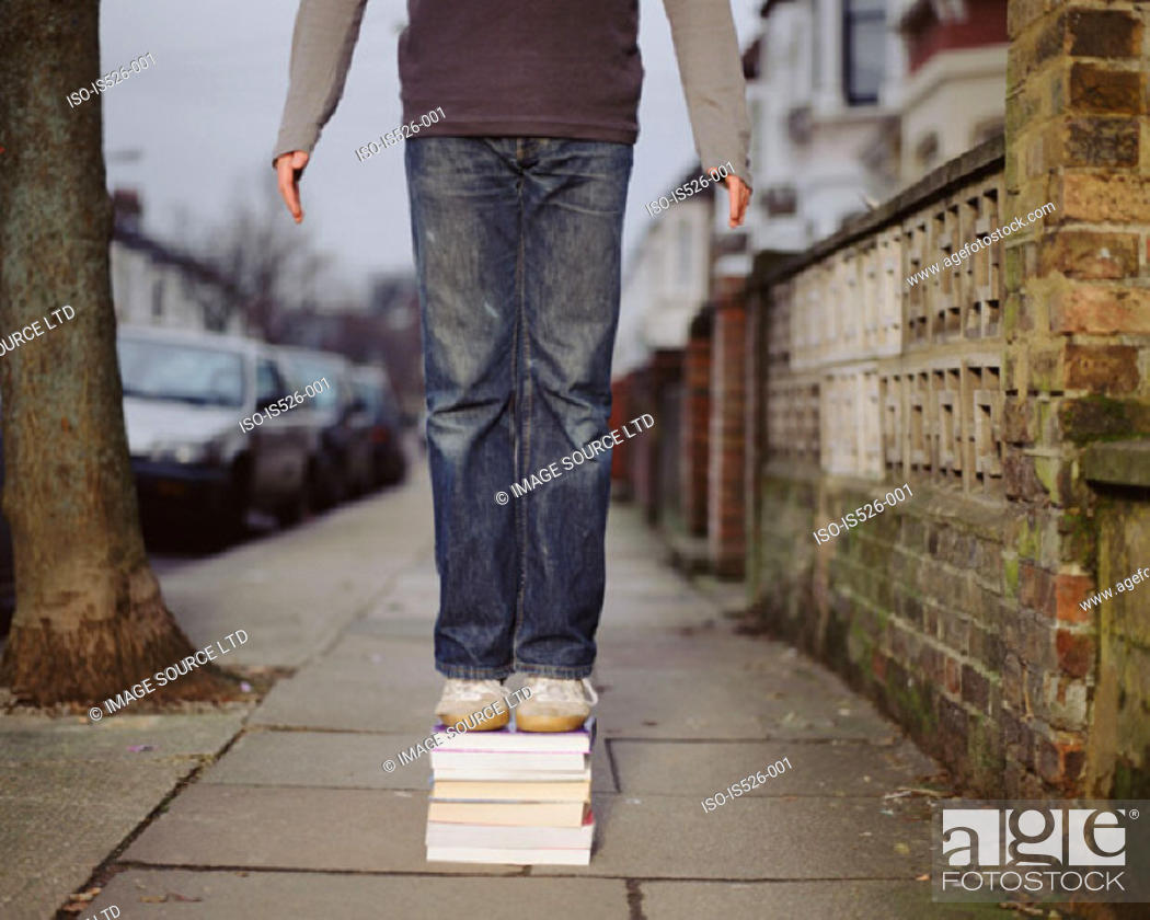 Stock Photo: A young man standing on a pile of books.