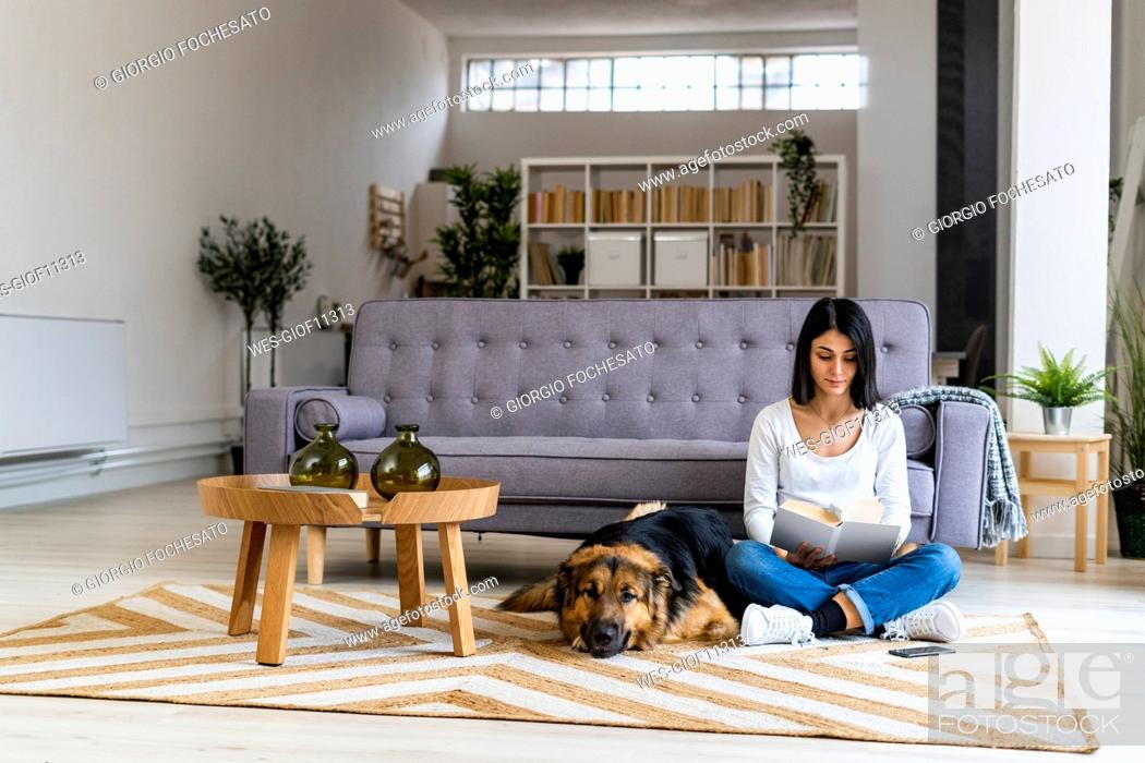 Stock Photo: Woman reading book while sitting with dog against sofa at home.
