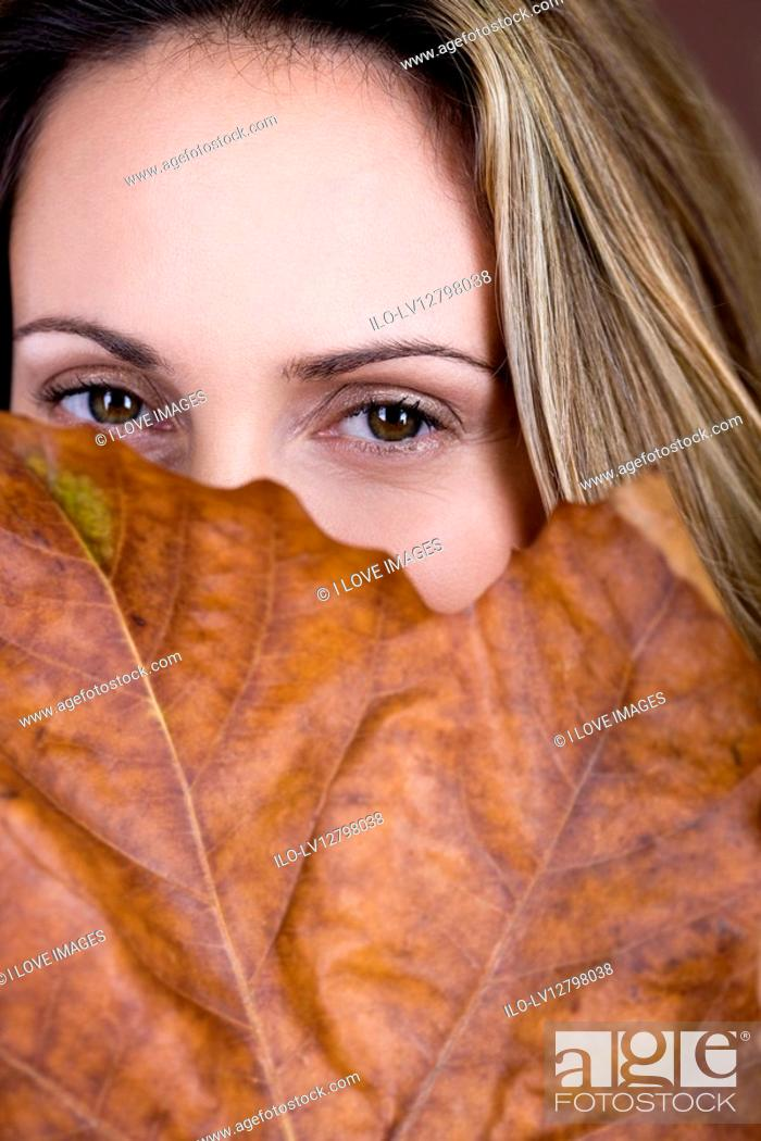 Stock Photo: A mid adult woman looking over a dried leaf.