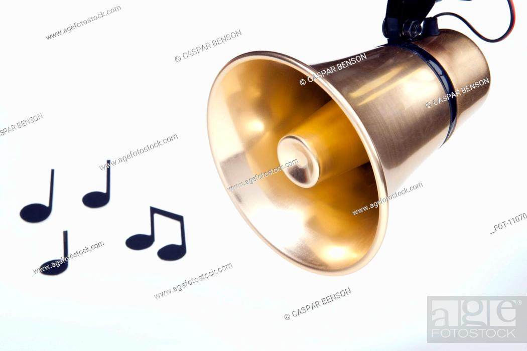 Stock Photo: A gold loudspeaker hanging next to musical notes.