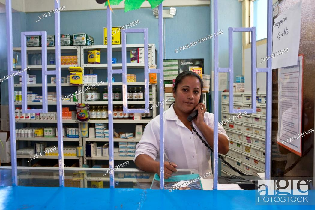 Stock Photo: El Milagro, Guatemala, a pharmacist is on the phone taking an order.