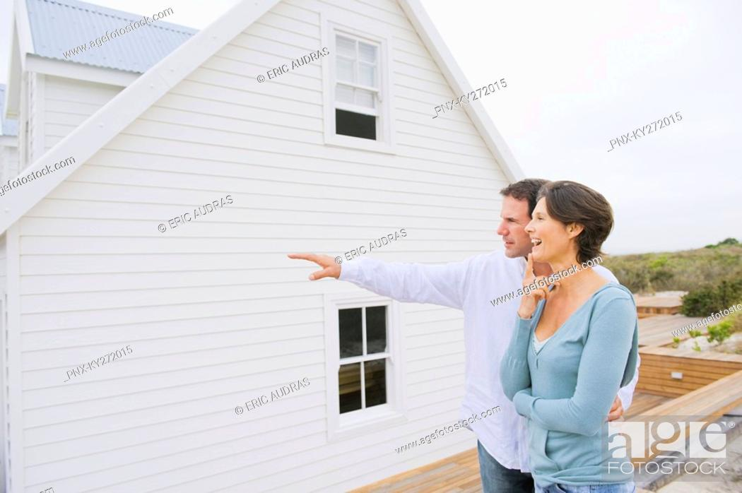 Stock Photo: Man pointing towards a house with a woman standing beside her.