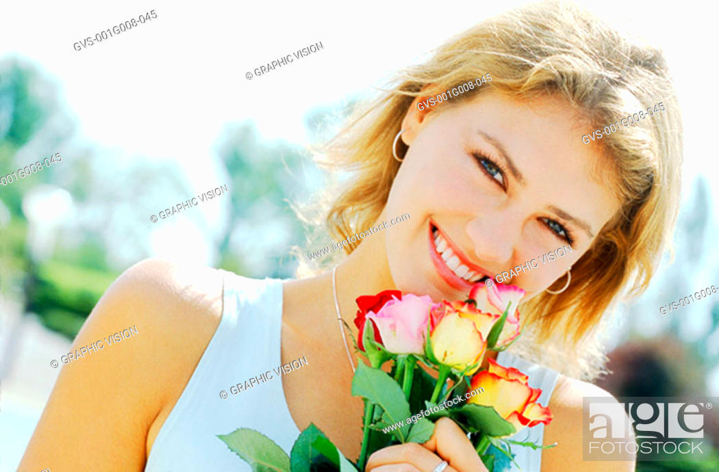Stock Photo: Portrait of a young woman holding a bunch of roses.