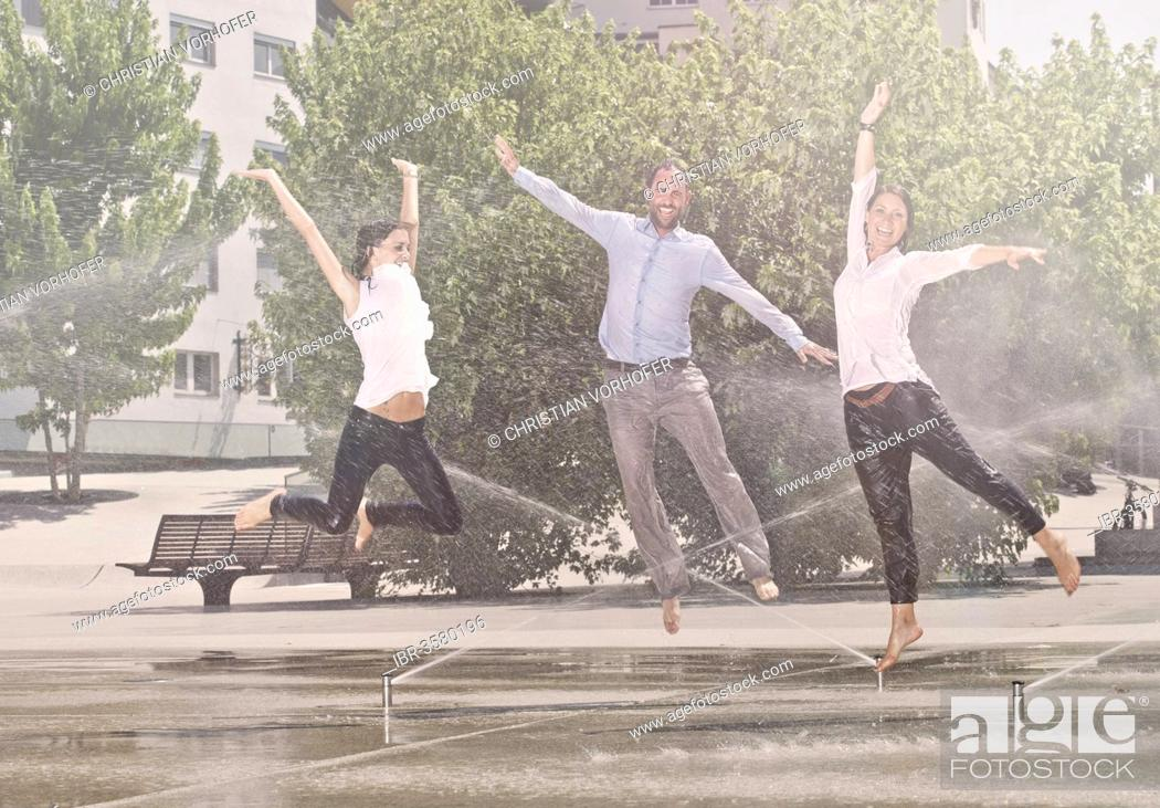Stock Photo: Two women and one man jumping in the park, between water sprinklers.