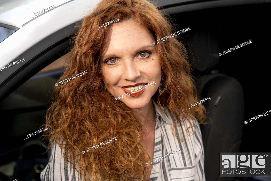 Imagen: A beautiful 41 year old redheaded woman, looking at the camera in the driver's seat of a car.