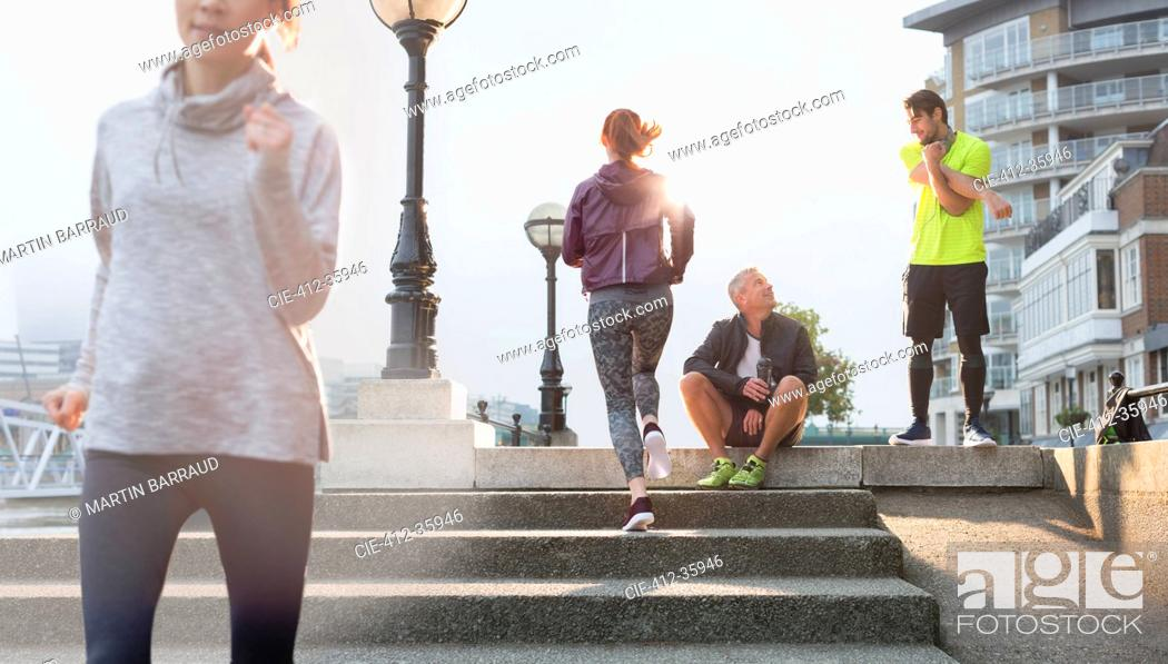 Photo de stock: Runners resting, stretching and running on sunny urban steps.