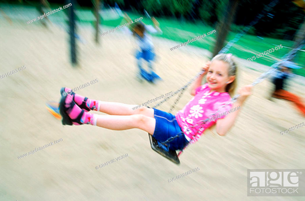 Stock Photo: Young girl playing on a swing.