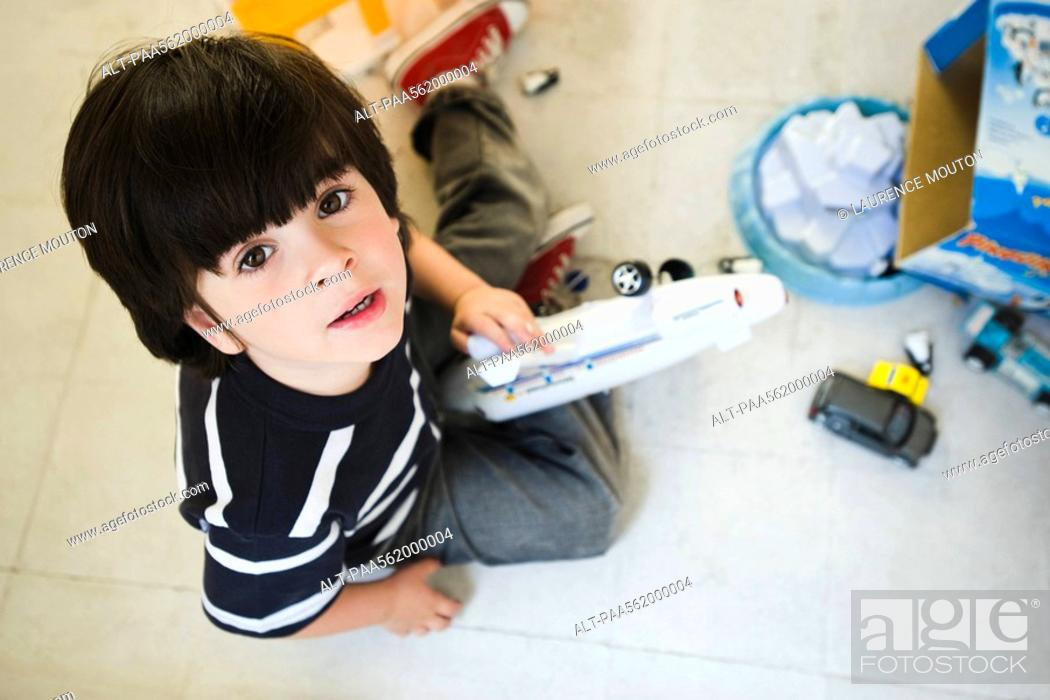 Stock Photo: Little boy sitting on floor playing with toys, looking up at camera.