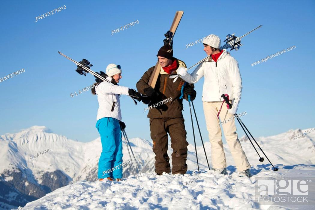 Stock Photo: Couple and daughter carrying skis.
