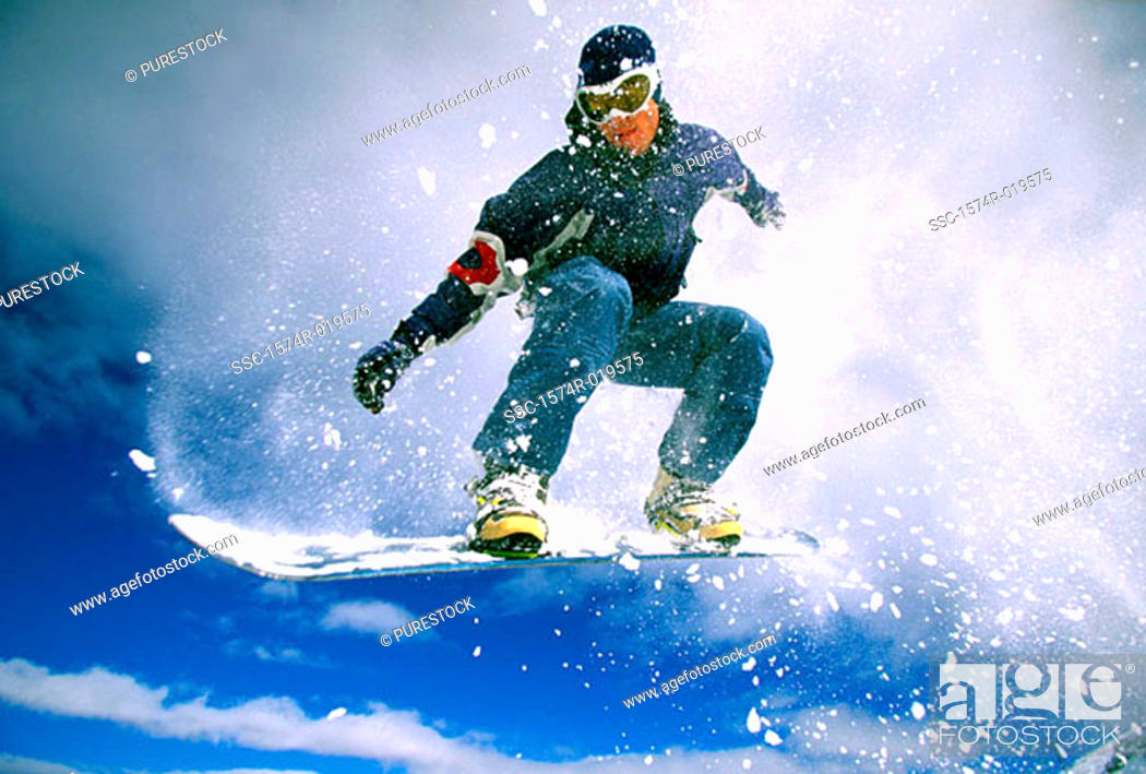 Stock Photo: Low angle view of a young man snowboarding.