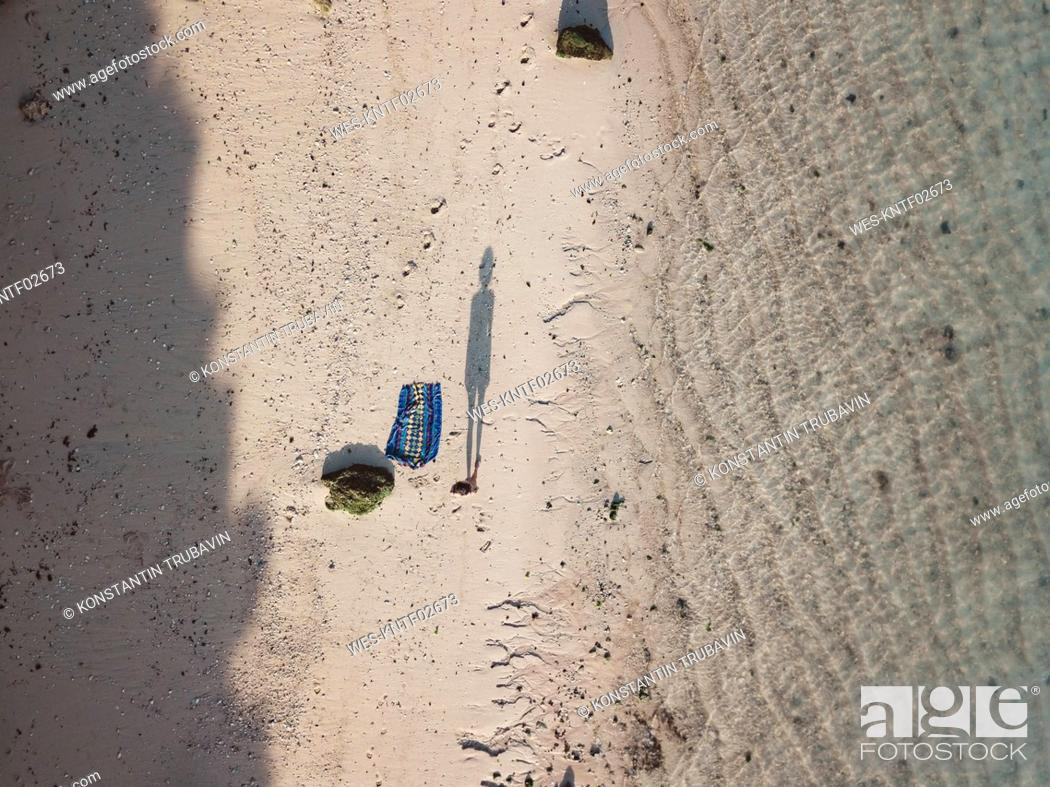 Stock Photo: Shadow of woman standing on the beach, top view.