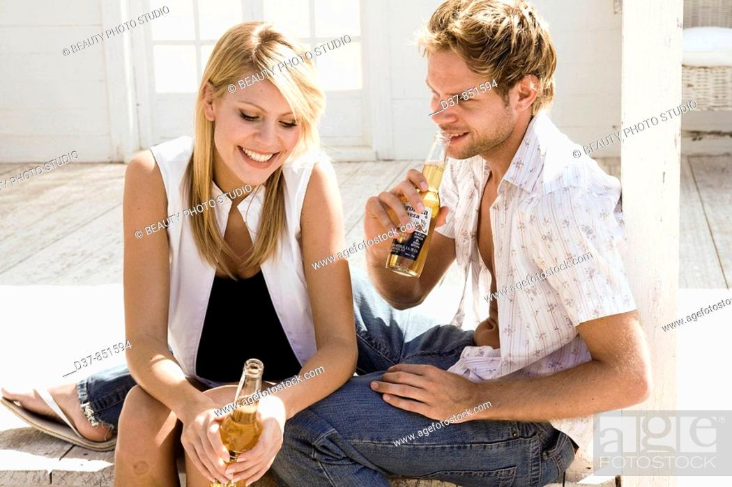 Stock Photo: Happy couple having a beer at home.