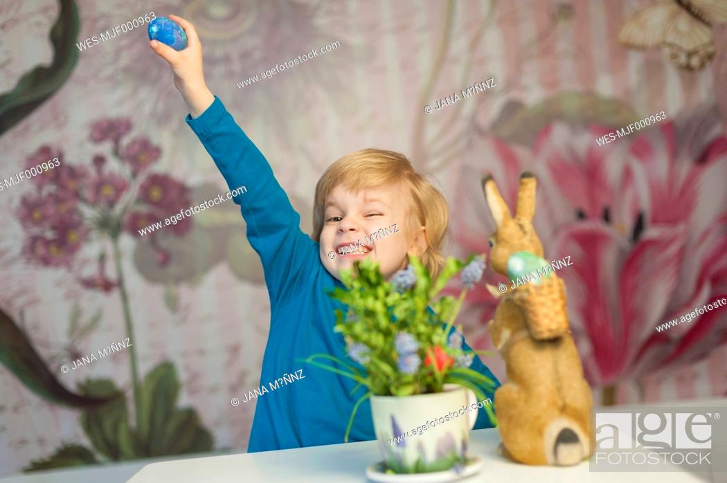 Imagen: Happy blond boy with Easter bunny holding egg.