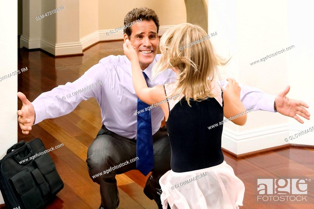 Stock Photo: Businessman receiving a warm welcome from his daughter.