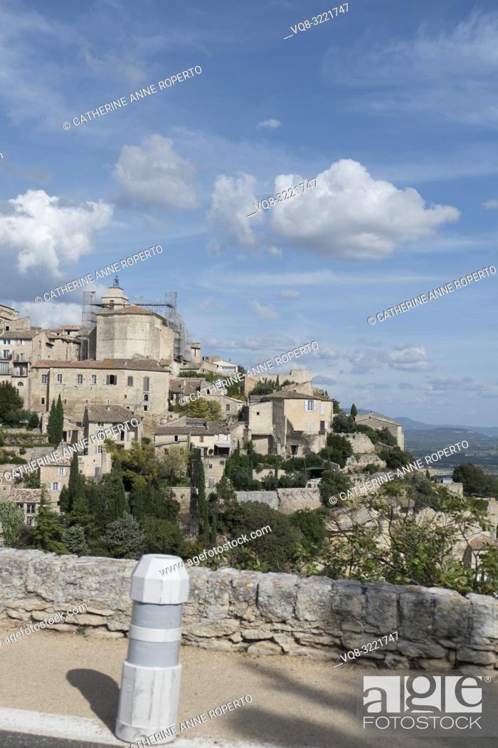 Stock Photo: Sky blue day with puffy white clouds and long shadows, tumbling down the hillside past the historic mountain town of Gordes in the Vaucluse.
