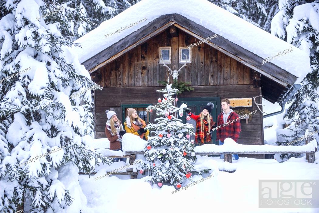 Stock Photo: Austria, Altenmarkt-Zauchensee, friends decorating Christmas tree at wooden house.