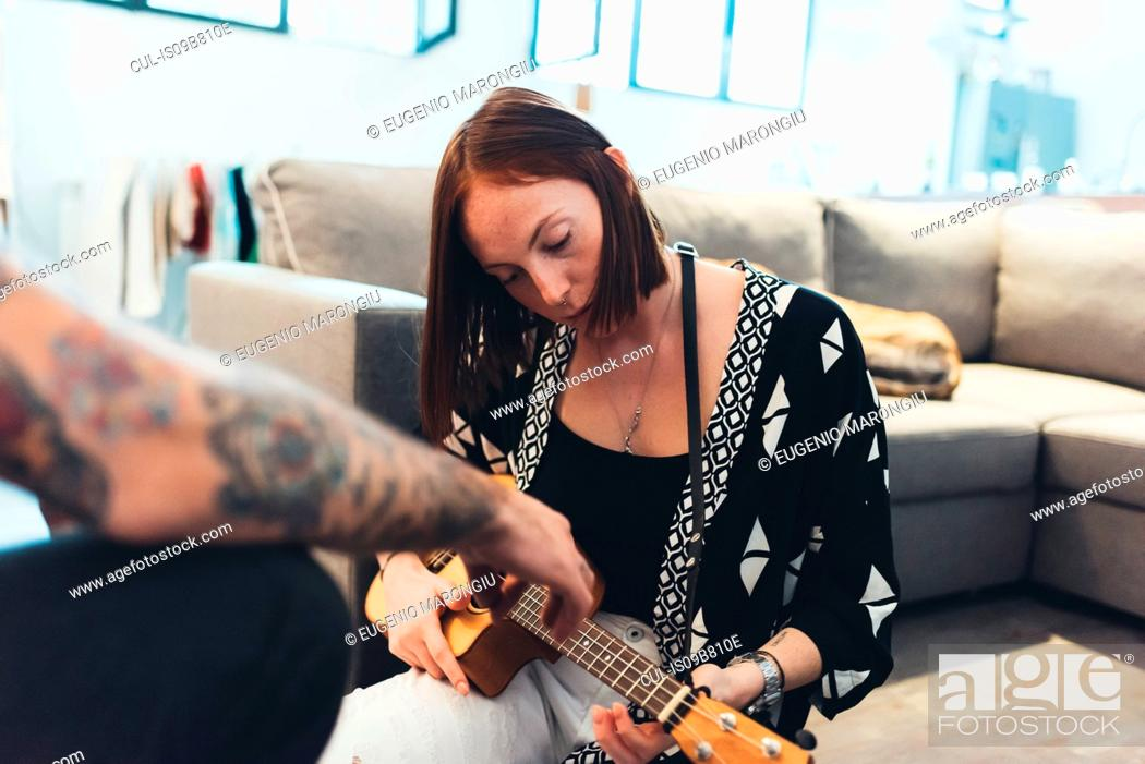 Imagen: Young woman in apartment learning to play ukulele from boyfriend.