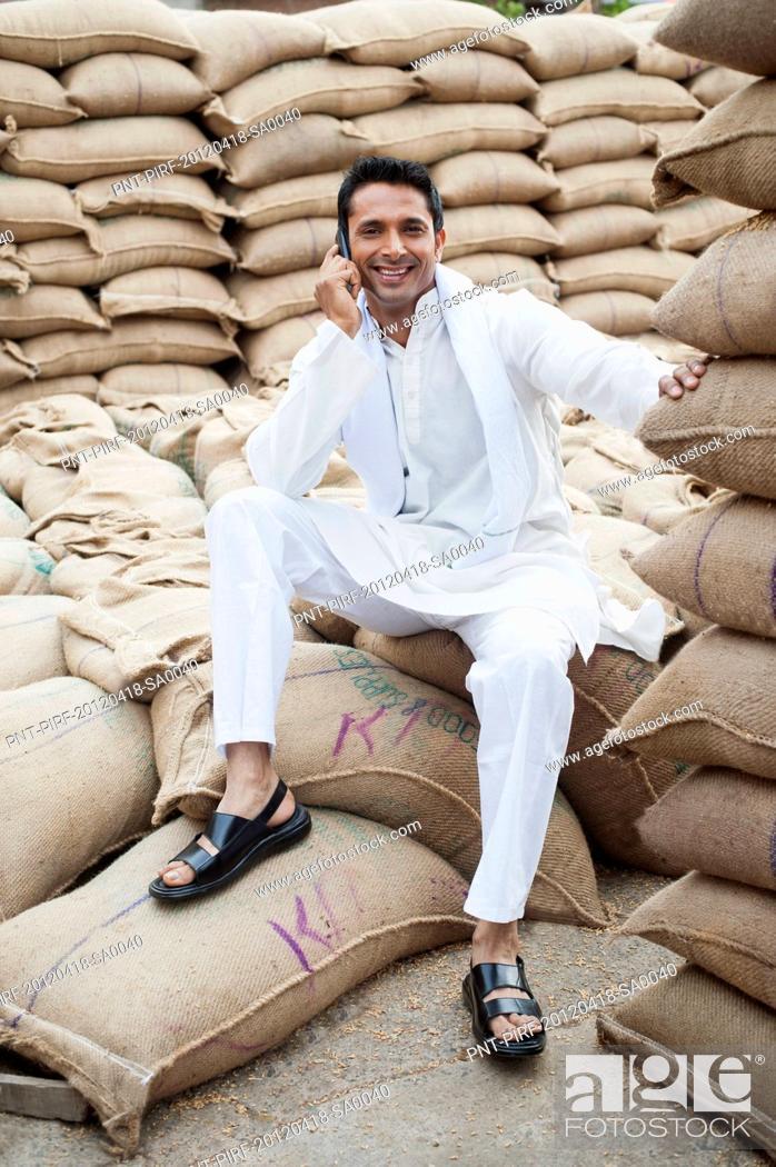 Stock Photo: Man sitting on a sack of wheat and talking on a mobile phone in a warehouse, Anaj Mandi, Sohna, Gurgaon, Haryana, India.