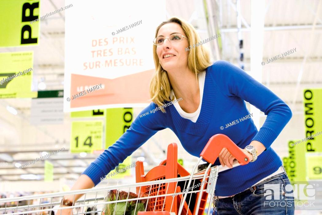 Stock Photo: Woman with shopping cart in supermarket.