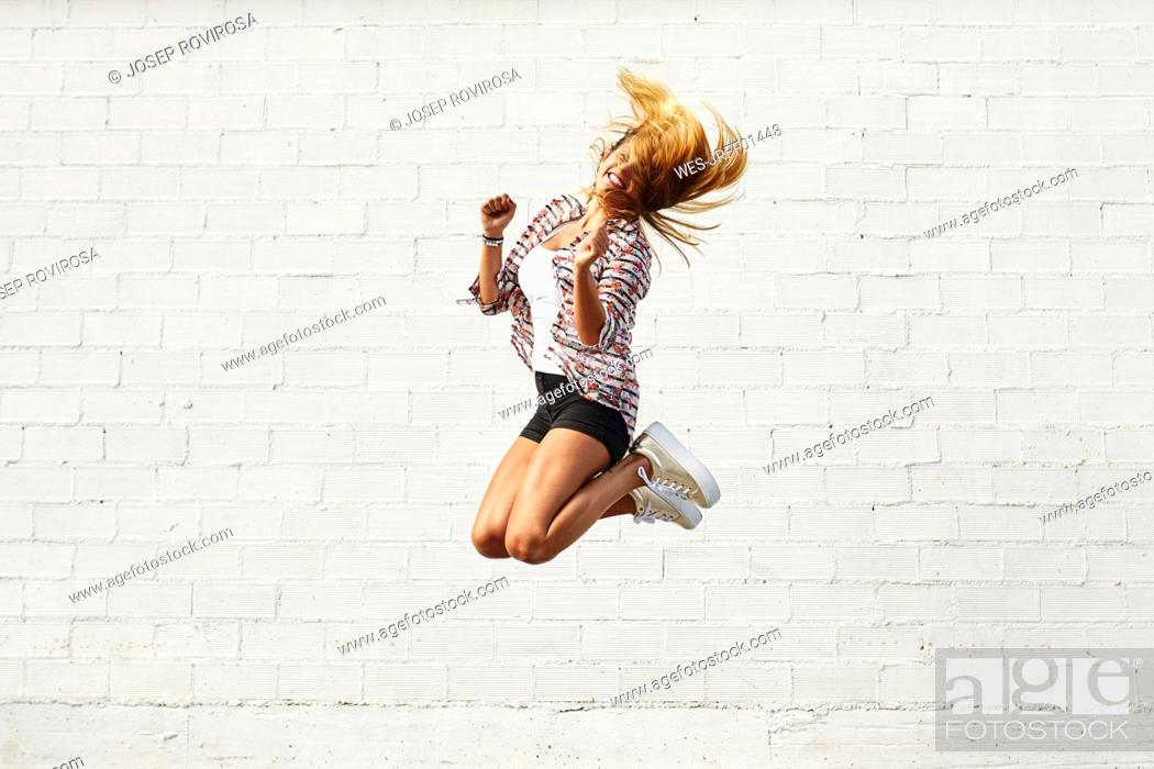 Stock Photo: Happy young woman jumping mid-air in front of white wall.