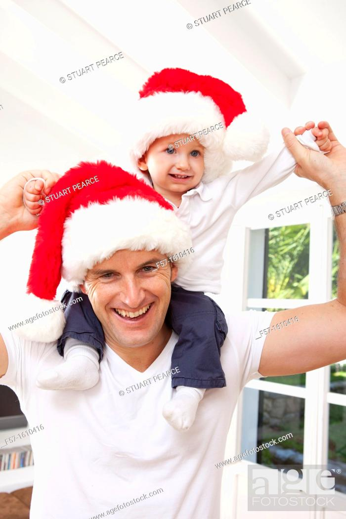 Stock Photo: One year old boy on his fathers shoulders at Christmas time.